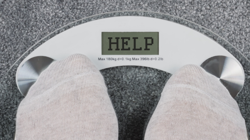 Diet. A person steps on the digital scales to check her weight. Inscription Help on a digital display, conceptual footage. First-person view from above Royalty-Free Stock Footage #1060599712