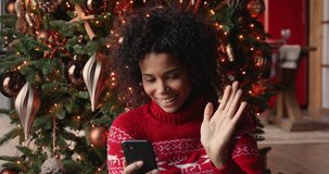 African woman holds smart phone make video call on Christmas Eve congratulates relatives 2021 enjoy remote talk dances feels cheery celebrates New Year, videocall and modern comfort tech usage concept