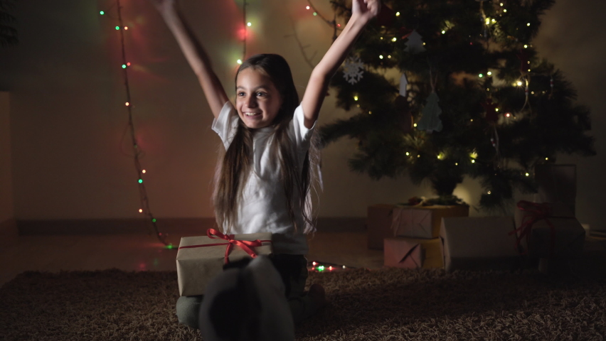 A little girl sits near the Christmas tree, raises her hands up, rejoices at the gift. Dog jack russell