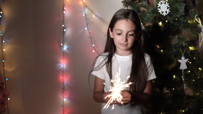 A little girl stands near a Christmas tree holding burning sparklers in her hands
