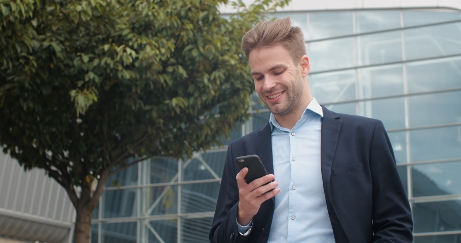 Handsome Young Businessman is texting Messages on his Smartphone, walking near Glass Office. Caucasian Male wearing Suit. Wind blowing his Hair. Business. Phones. Success. Royalty-Free Stock Footage #1060603123
