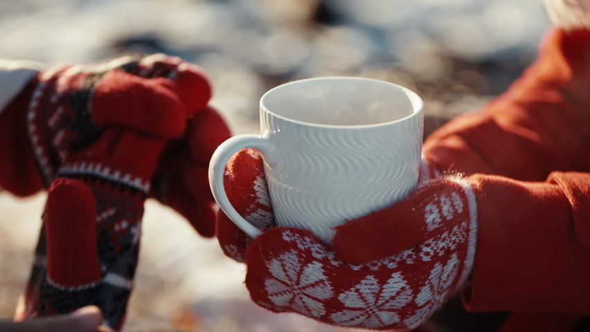 Close up hands of couple holding cups with hot tea at winter days. Coffee in the hands of a girl and a guy at xmas date. Freezing weather and warm hugs. Love concept. Royalty-Free Stock Footage #1060604356