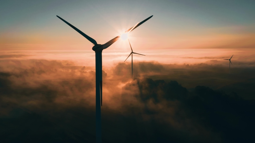 Wind turbines at sunrise in heavy fog. Wind farm generating green energy Royalty-Free Stock Footage #1060610539