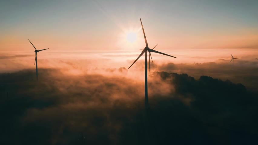 Wind turbines at sunrise in heavy fog. Wind farm generating green energy   Shutterstock HD Video #1060610551