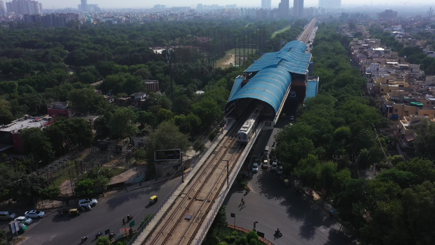 An aerial shot of the Delhi Metro leaving the station in New Delhi, India Royalty-Free Stock Footage #1060612588