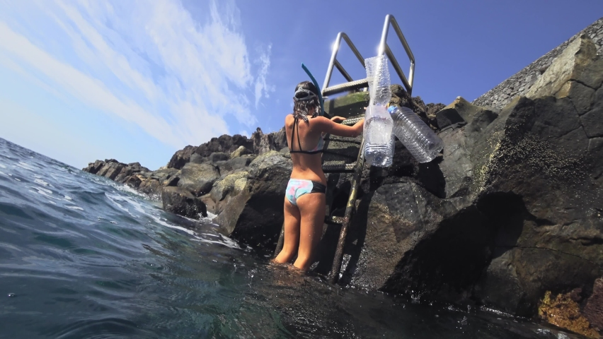 Clear the Ocean of Plastic Young girl volunteers with cleaning net cleaning up rubbish garbage in sea. Ecology, people, volunteering, charity, cleaning, nature concept 4k | Shutterstock HD Video #1060612783