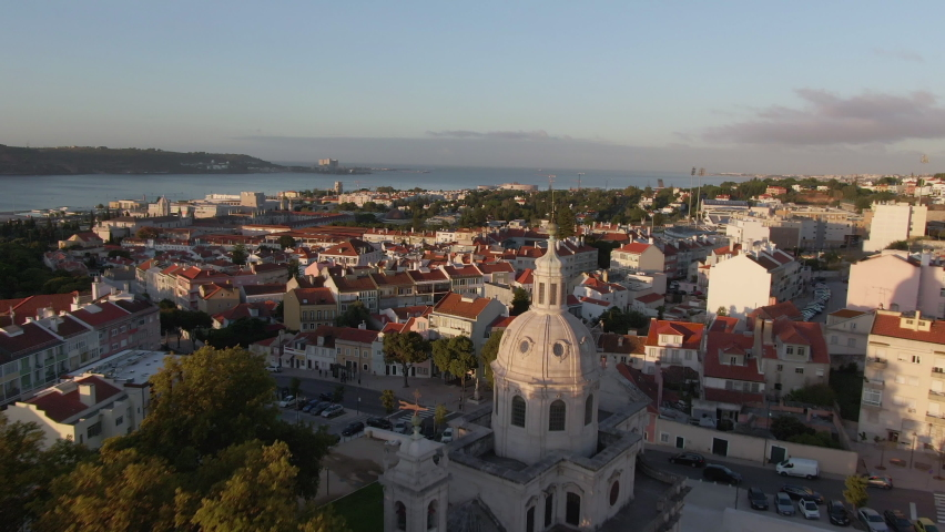 Aerial view of Lisbon, Portugal, flying over architectural landmark Memory Church (Portuguese: Igreja da Memoria ) towards the famous Belem district at sunrise. Royalty-Free Stock Footage #1060613653