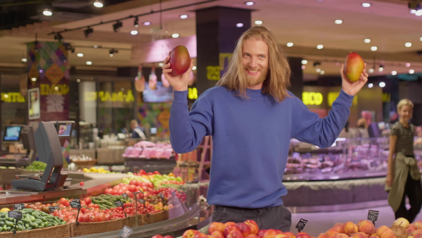 Young blond bearded man dressed in casual sweater happily dancing with mangoes in hands during shopping in modern grocery store. Funny concept Royalty-Free Stock Footage #1060614214