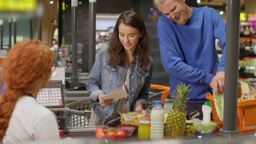 Young attractive couple with checklist laying out goods at the checkout in modern grocery store. Young family on shopping in supermarket Royalty-Free Stock Footage #1060614220