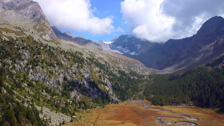 Val Masino, province of Sondrio, Italy, September 2020: aerial view of an alpine valley with a river of okurkhon conifers. Glaciers. Nature. Green Planet. Mountain river. Meditation and relaxation | Shutterstock HD Video #1060621411