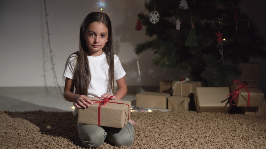 Little girl sitting near the christmas tree, pet, dog jack russell comes up to her