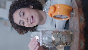 Savings, money saving concept. Young woman is throwing money in the money box.Video for the vertical story.