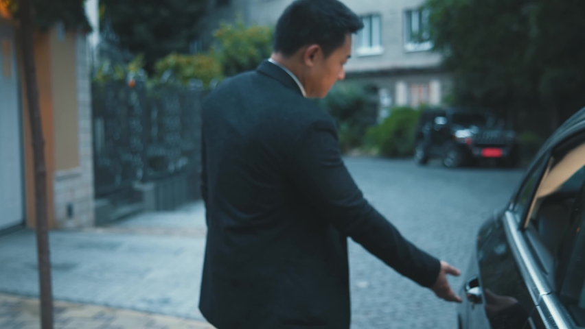 Legs of office person businessman standing on street when taxi arriving. Asian corporate entrepreneur entering the car commuting to work. Cityscape. Transportation concept. Royalty-Free Stock Footage #1060629634