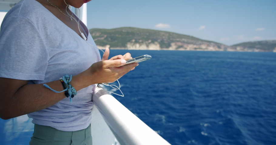 Woman using her smart phone on travel by cruise ship. Close up shot of woman's hands with mobile phone.
