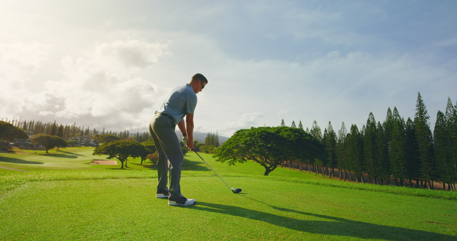 Man playing golf at sunrise, swinging and hitting golf ball, slow motion