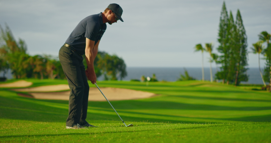 Man playing golf on beautiful luxury resort golf course, swinging and hitting golf ball in slow motion