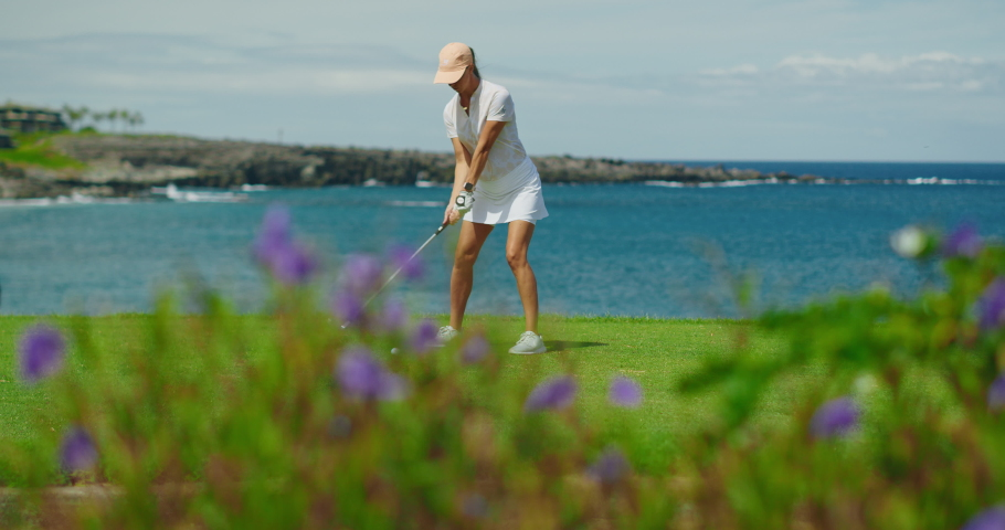 Woman playing golf on beautiful course on the ocean, swinging and hitting golf ball in slow motion, luxury resort vacation