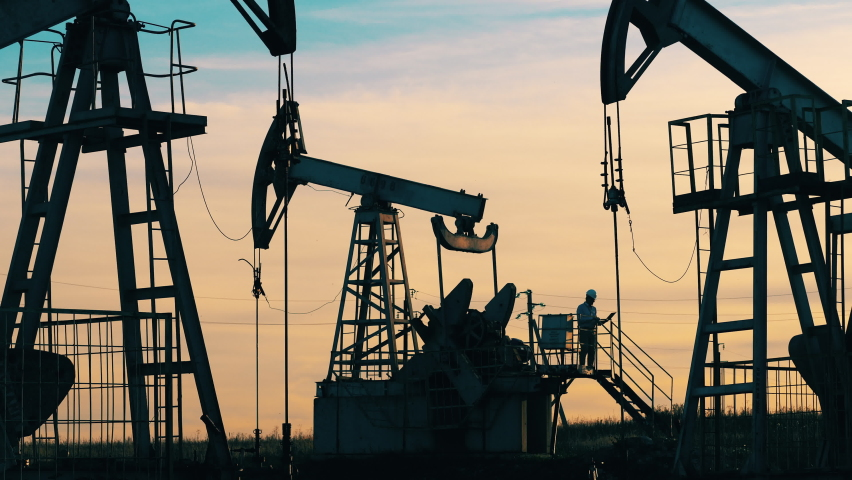 Oil worker standing among the oil pump jacks. Oil industry, crude oil prices concept. Royalty-Free Stock Footage #1060636072