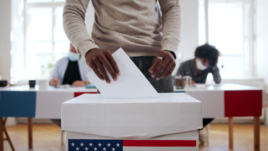 Unrecognizable african-american man putting his vote in the ballot box, usa elections and coronavirus. Royalty-Free Stock Footage #1060641034