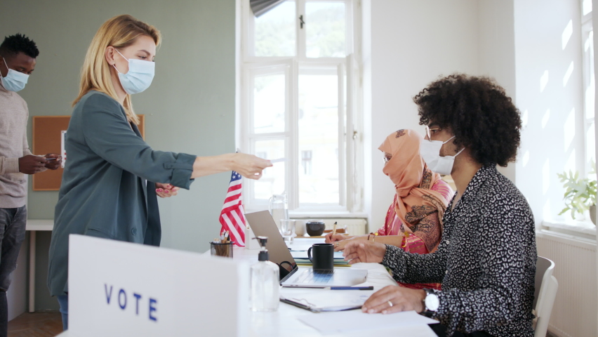 People with face masks voting in polling place, usa elections and coronavirus. Royalty-Free Stock Footage #1060641100
