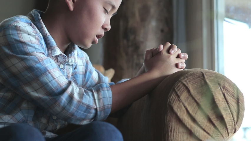 Boy praying on sofa at home, church in home, Home church during quarantine coronavirus Covid-19, Religion concept. Royalty-Free Stock Footage #1060642153