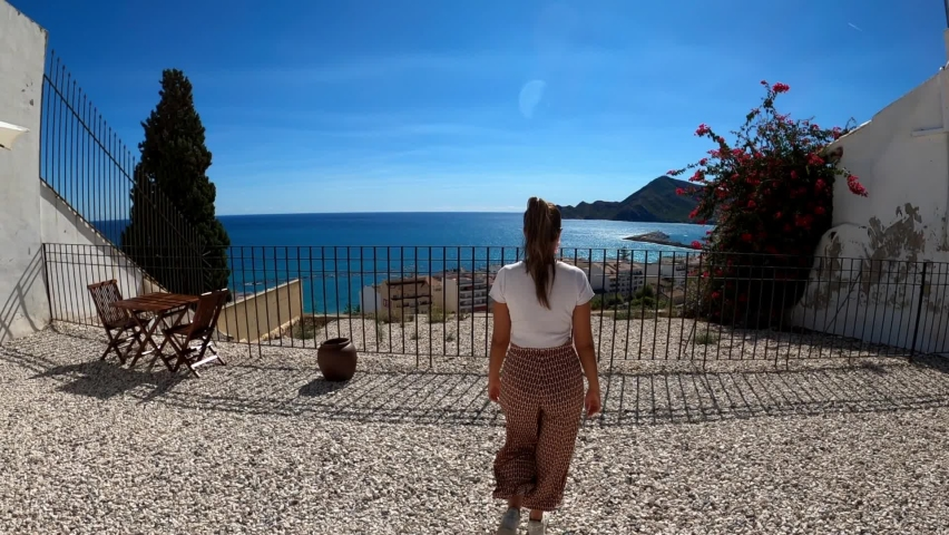 Tourist woman looking at Altea coast over terrace in Altea old town. Altea old town street walking POV or point of view. White architecture of old-town in cobblestone Royalty-Free Stock Footage #1060644622