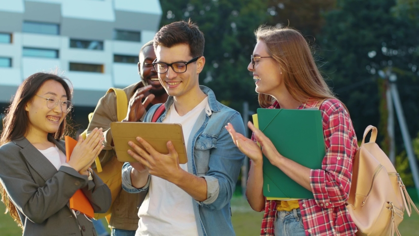 Happy caucasian man student showing to company of students his newest project browsing laptop presentation rejoicing achievement. Friendship. Connevction. Goals. Education concept. | Shutterstock HD Video #1060649215