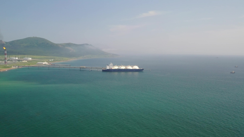 Day, filming from a quadrocopter in a spiral, on the coast of the Okhotsk sea at the pier of a liquefied natural gas plant in the city of Korsakov there is a gas tanker, several tugboats are nearby