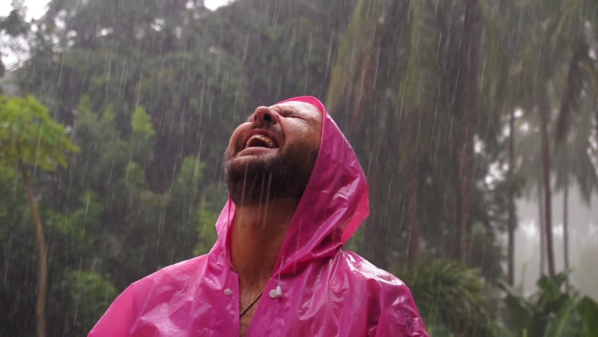 An adult man in a pink raincoat enjoys the tropical rain. Slow motion. High quality FullHD footage Royalty-Free Stock Footage #1060651684