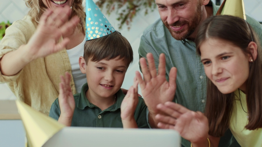 Portrait of cheerful parents and children waving hands at webcamera connecting friends online congratulate with birthday holidays. Celebration. Emotions. Families concept. Royalty-Free Stock Footage #1060652794