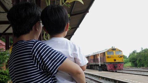 4K Asian father and cute child boy wait to see train at railway station outdoor. Dad carrying son travel outdoor. Happy family activity and learning concept. Train coming in the end.