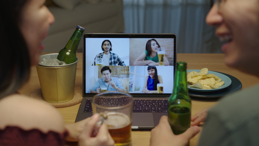 Slow motion : Young happy asian couple enjoy relax night party event online celebration festive with friends at home clinking beer with glass and bottle toasting drinking via video call. | Shutterstock HD Video #1060660261