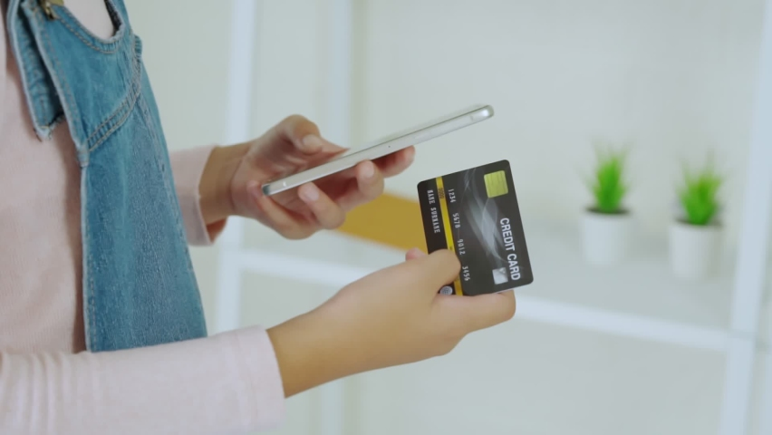 Close up young woman holding credit card using mobile phone typing number payments at home. Zoom hand girl customer purchase, shoping online food delivery, hotel booking, buy application by smartphone Royalty-Free Stock Footage #1060660264