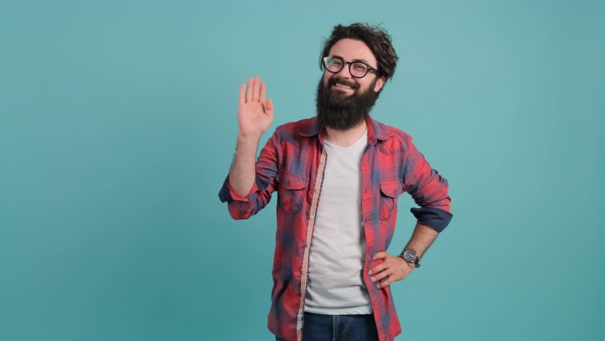 Hello. Friendly bearded man saying hi and smiling, welcoming friends with raised hand. | Shutterstock HD Video #1060660324