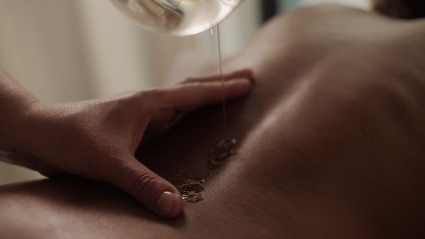 Closeup masseur hands pouring massaging oil to female back preparing to relaxing or revitalizing massage procedure at spa beauty salon pleasant woman lying on couch enjoying skin and body care   Shutterstock HD Video #1060662412