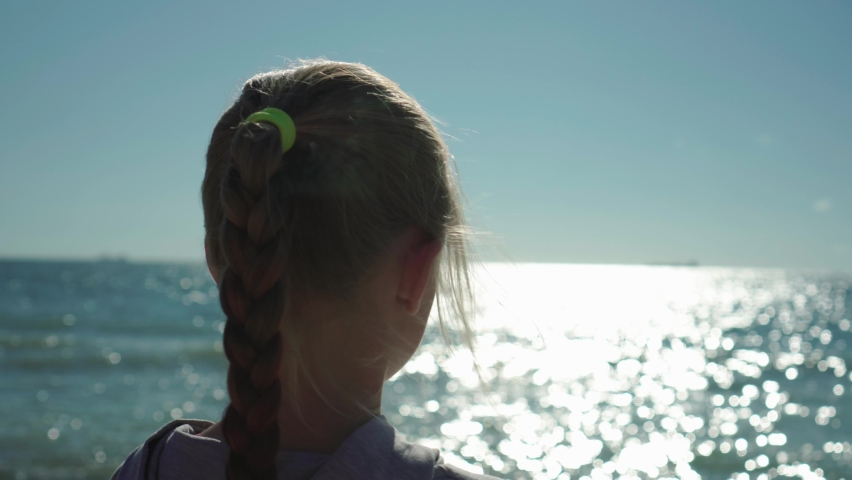 Close up of blonde child girl with braid looking at the sea water shimmering at sunset. Wind in her hair. Dreaming of future concept   Shutterstock HD Video #1060662775