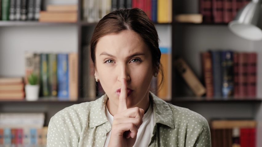 Shh, woman secret finger. Suspicious woman in office or apartment looks at camera and brings her index finger to her mouth lips and she say shhh | Shutterstock HD Video #1060664227