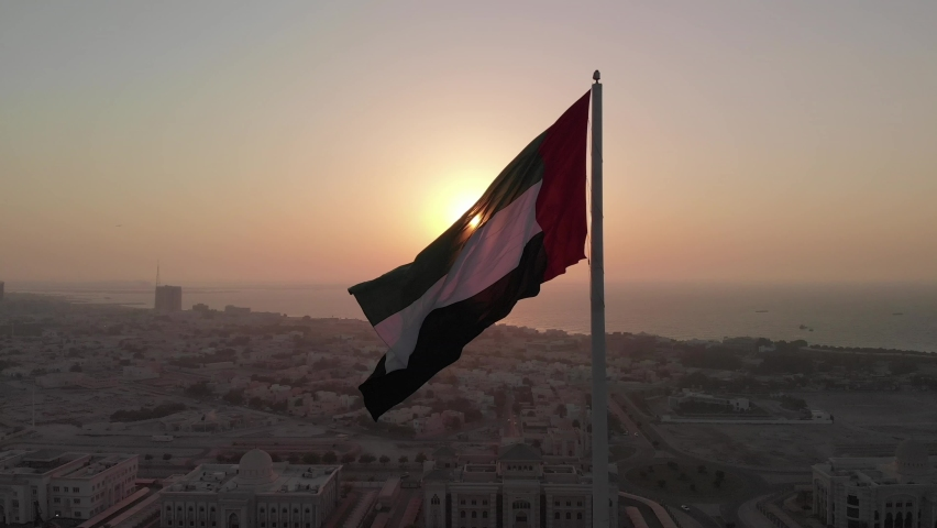 Silhouette, Flag of the United Arab Emirates waving in the wind, Sky and Sun Background, The national symbol of UAE over Sharjah's Flag Island, United Arab Emirates, 4K video
