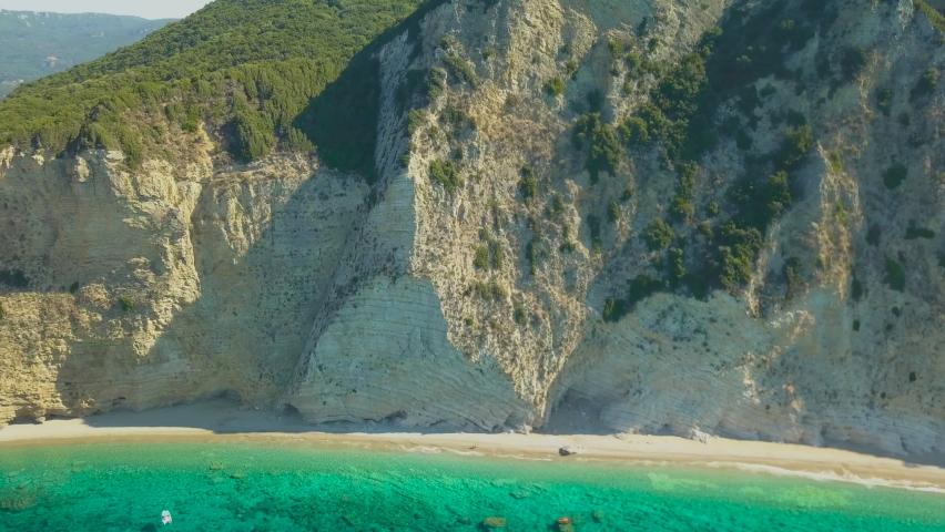 Aerial drone pullback revealing beach Blue Lagoon along cliff on Mediterranean / Ionian sea coast of the Greek Island of Corfu / Korfu / Kerkyra on a sunny day Paleokastritsa / Palaiokastritsa beach   Shutterstock HD Video #1060666519
