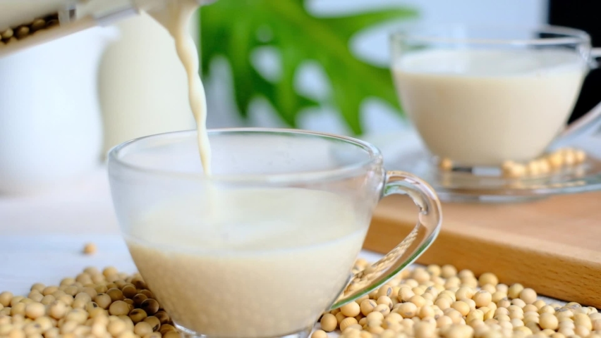 Soy milk / Bean milk poured into glass cup. Soy milk considered as plant-based drink for healthy vegetarian. Drinking hot soya drink or soy milk in morning is healthy. Plant based diet concept. Royalty-Free Stock Footage #1060668847