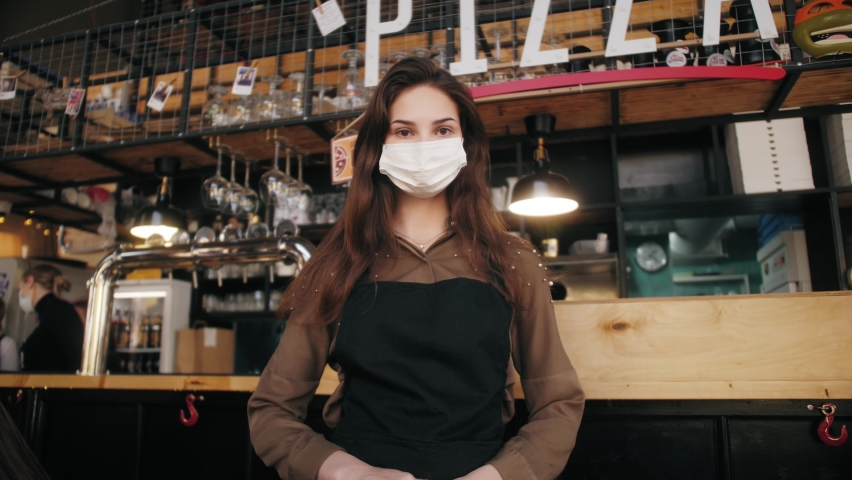 Portrait of owner woman cafe wearing face medical mask, Cafe staff working in protective masks. Owner pizzeria. New Life After Covid-19. Business reopen after coronavirus quarantine is over. Royalty-Free Stock Footage #1060670026