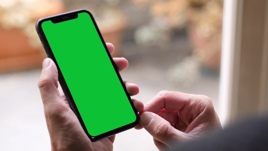 Italy - 2020: Single Tapping and Holding a Green Screen iPhone