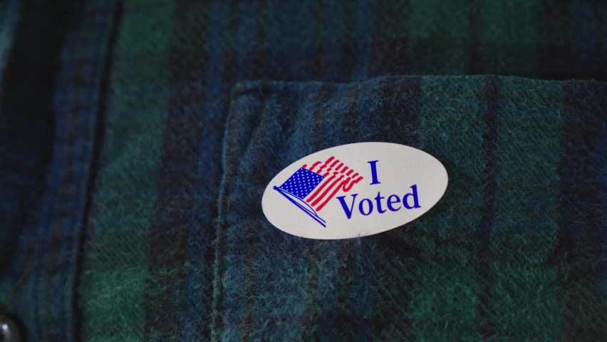 Man puts I Voted Sticker on Clothing After voting in American Democratic Election, doing one's civil duty Royalty-Free Stock Footage #1060675135
