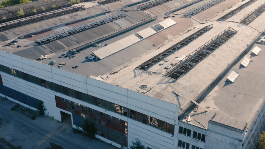 Abandoned ruined concrete warehouse or production department on the factory territory. Old industrial edifice for demolition. Aerial view
