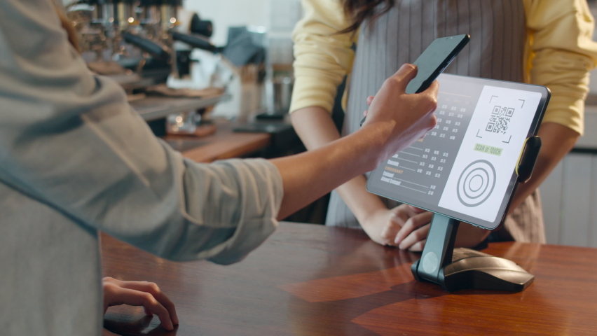 Young Asia female self service use mobile phone pay contactless with tablet at cafe restaurant. Girl barista talking receive orders from customer at bar counter in coffee shop. Owner small business. Royalty-Free Stock Footage #1060681993