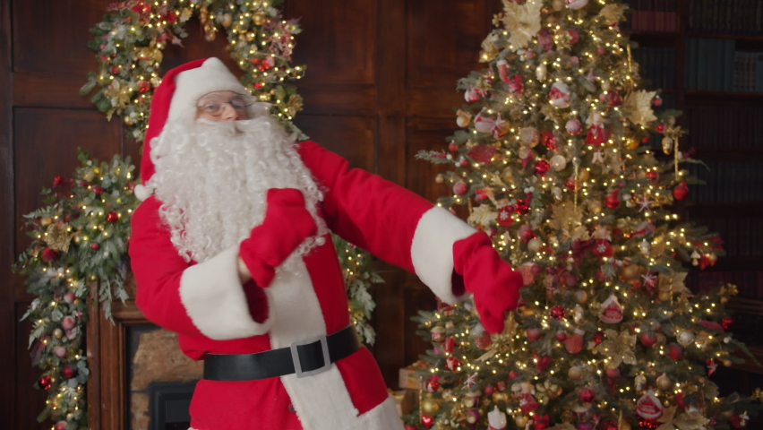 Slow motion portrait of modern Santa Claus dancing in decorated apartment near Christmas tree with balls and lighs. Celebrations and joyful people concept.