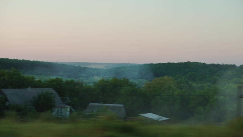 Transport, travel, road, railway, landscape, comnication, disasters, cataclysms concept - view from window of speed train on forest in smoke from beginning fire in sunny clear weather summer evening