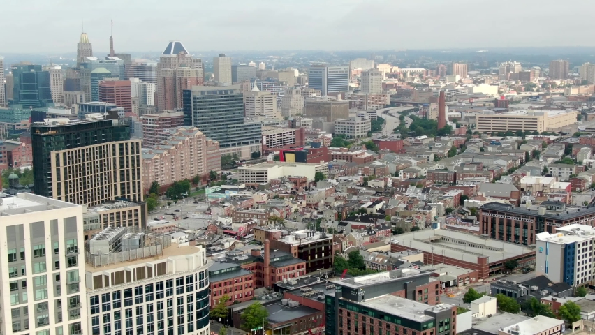 Cinematic high aerial of downtown Baltimore skyline and cityscape, financial center skyscrapers, highway, residential homes in Fells Point neighborhood