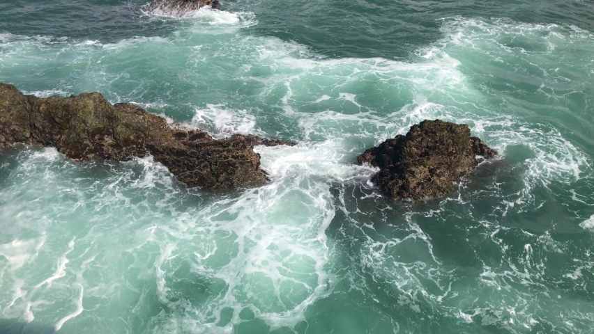 Waves in strong swirling undertow current violently splashing emerald green saltwater and sea foam mist on rough coastal rocks on a hot summer day.