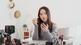 Young beautiful Asian woman beauty vlogger influencer recording make up tutorial video clip with mobile phone in her bedroom at home